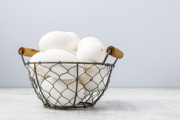Basket of big white goose eggs.