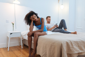 Young beautiful interracial couple in bed stressed with infidelity problems .