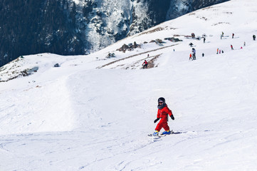 Little child going down from snowy hill