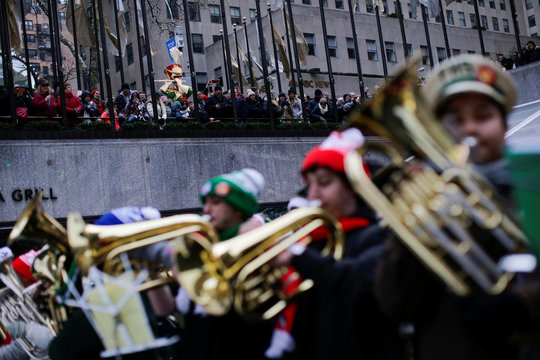 People watch hundreds of tuba players perform Christmas carols during the 44th Annual Merry Tuba Christmas at Rockefeller Center in the Manhattan borough of New York