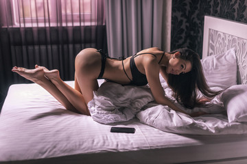 girl in black lingerie on the bed standing in a sexy pose doggy style