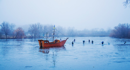 A wooden boat in the river with ice in the evening in the winter foggy day