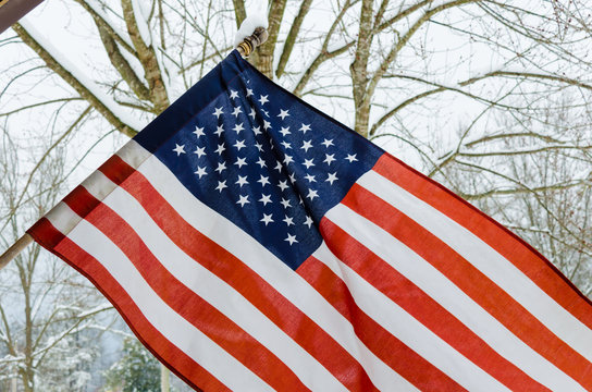 American Flag with winter snow background. Celebration national USA Holiday and patriotic pride.