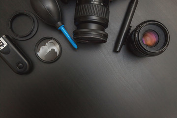 top view of work space photographer with dslr camera system, camera cleaning kit and camera accessory on black table background with copy space
