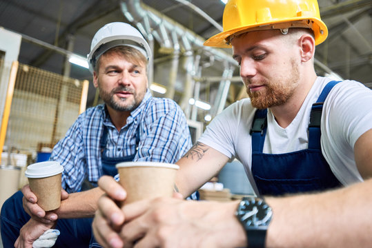 Portrait of two workers wearing hardhats taking break from work drinking coffee and resting sitting on construction site