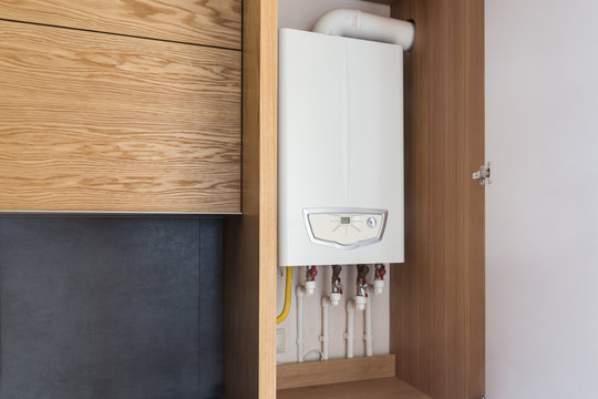 Opened kitchen cabinet and a gas boiler, a smart solution to hide the boiler inside furniture. Kitchen in a modern loft style with wooden details.