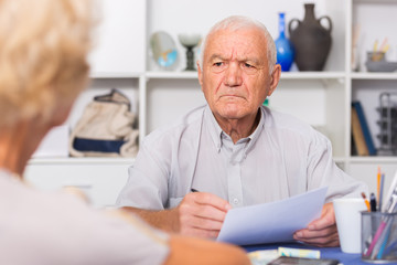 Upset senior man discussing with wife bills