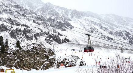 Red cable car in the background of the winter mountains.  Old red cable car at mountain. Ski resort Maso Corto, Italy, Trentino alto Adige.  Red cable car in the mountains in winter