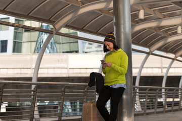 Happy traveler using a smartphone in city building while is waiting for transport