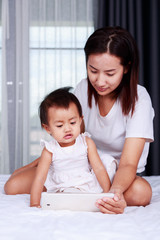 Mother and baby are looking to play and read tablet computer at home