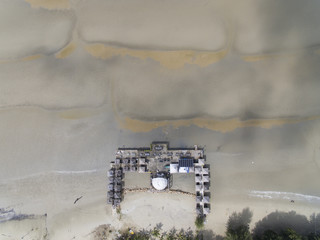aerial view of a pier at low tide beach