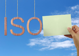 Wooden ISO text Stands for International Organization for Standardization hanging on rope.