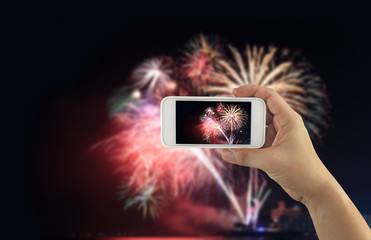 hand of a businessman holding a smartphone to take a pictures at night and fireworks on dark sky.