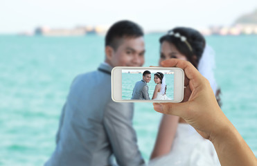 hand of a businessman holding a smartphone to take a pictures of asian love couple.