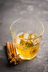 Glass with whiskey on the rustic wooden background. Selective focus. Shallow depth of field.