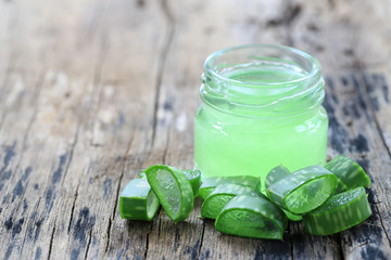 Fresh aloe vera and jelly in Glass bottle placed on a wooden floor.