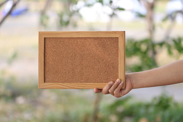 Hand of a business woman holding a empty wooden picture frame on blur garden background.