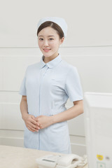 The young woman nurse is at the reception desk