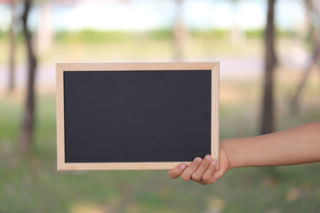 Hand of a business woman holding a empty black wooden picture frame on blur garden background.