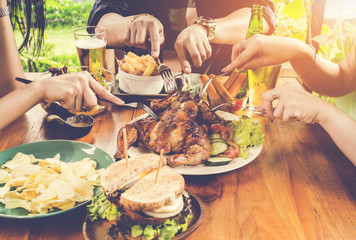 Close up hand, eating.Group Of People Dining Concept,With  Chicken roasting,salad,French fries on wooden table