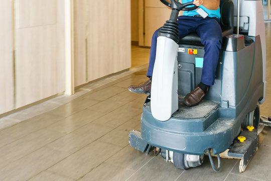 unidentified man operates rider floor Scrubber Machine at supermarket