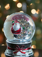 Snow Globe with an Ice Skating Santa with a Christmas tree with lights on in the background. Shallow depth of field.
