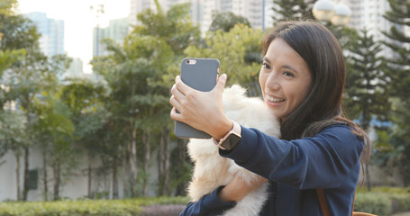 Woman taking selfie on mobile phone with her dog