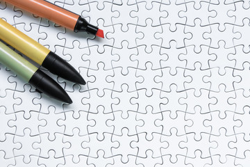 Colorful marker pen on white jigsaw puzzle background.