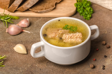 fresh transparent fish soup with sturgeon, potatoes in white plate, decorated garlic, parsley leaves and cutted rye bread, healthy eating