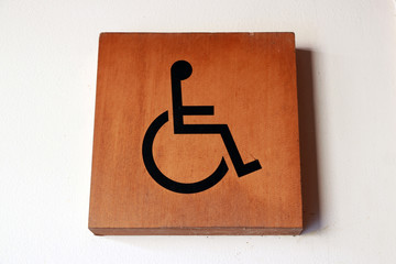Wooden handicapped mark on the wall in front of the Bathroom disabled. who having a physical or mental condition that limits movements or activities.
