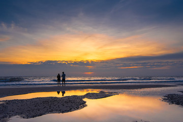 Romantic scene of a couple silhouette of a couple enjoying on the beach watching the sunrise in the morning.