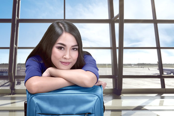 Smiling asian woman with suitcase waiting flight departure