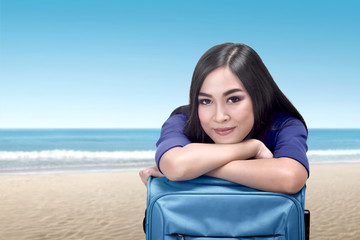 Young asian woman lean back on suitcase relaxing