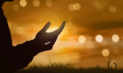 Silhouette of human hand with open palm praying to god