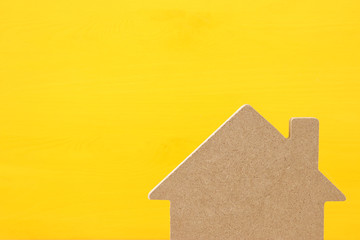 Image of wooden house model over yellow background. Real estate concept.