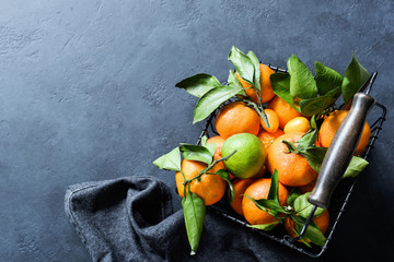 Fresh tangerines with green leaves in basket on dark backround. Top view with copy space for text