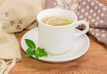 Cup of tea on background of woolen mittens and scarf