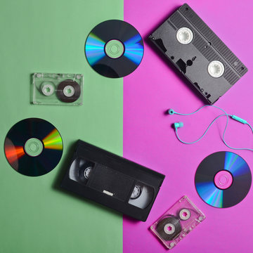 Retro devices on a pink mint pastel background. Audio cassettes, video cassettes, CD drives, headphones. Analog and digital technologies. Entertainment 80s. Watching movies and listening to music.