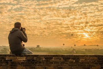 Male traveler photographing temples at Bagan Myanmar Asia at sunrise
