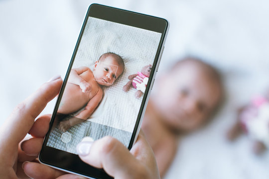 mother takes a photo of her newborn baby on a smartphone. family memories.