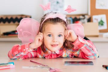adorable little girl get rest after art lesson. photo portrait of smiling cutie. creative space.
