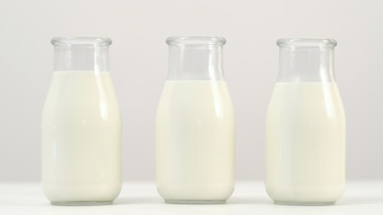 Three milk or yogurt bottles on white background. Selection of quality dairy products. Wide choice in shops. Copyspace concept