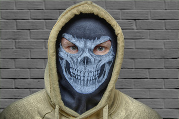 Man in balaclava skull mask and hood, maybe halloween costume (robber, burlgar, snatcher, terrorist or evil anonymous) with brick wall on back