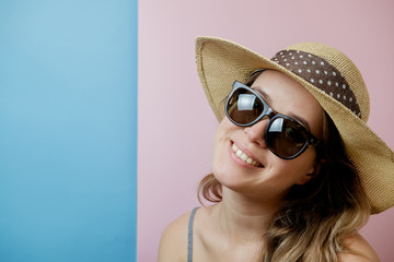 Portrait of young pretty model in sunglasses and hat