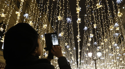 A woman takes pictures of festive decorations and illumination lights prior to the New Year and Christmas holidays in central Moscow