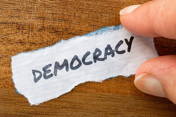 Democracy concept and theme written on old paper on a grunge background