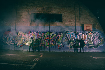 people holding smoke bombs and standing against wall with graffiti at night