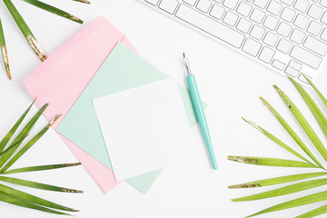 Bright flat lay fashion mock up: white keyboard, golden palm leaves, colorful cards, envelope and dip pen on white background. Text space