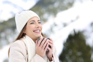 Woman keeping warm holding a cup of coffee in winter