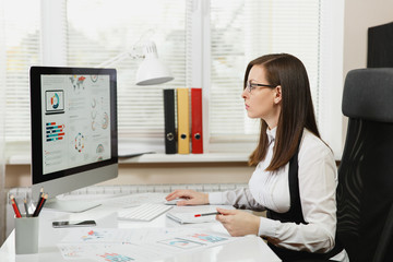 Beautiful business woman in suit and glasses working at computer with documents in light office, looking at the monitor